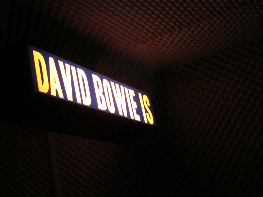 A sign from an art show, reading DAVID BOWIE IS.