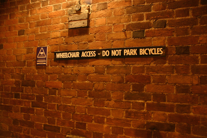 A sign advising people not to park their bicycles along a wheelchair ramp.