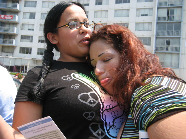 Two Latinas snuggling at a Pride parade.