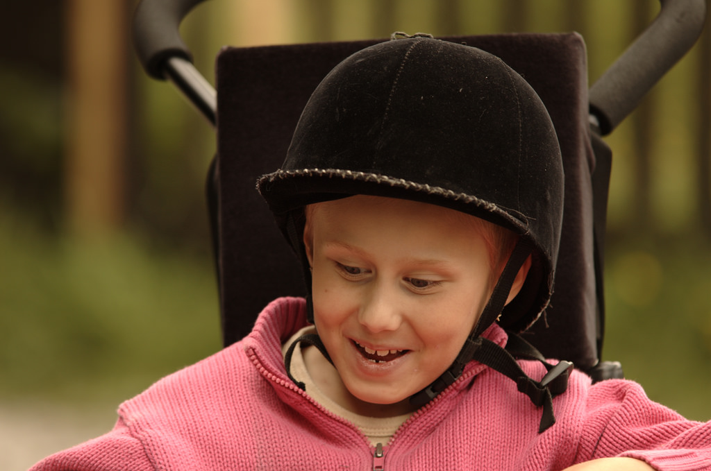 A disabled youth, smiling at the camera.