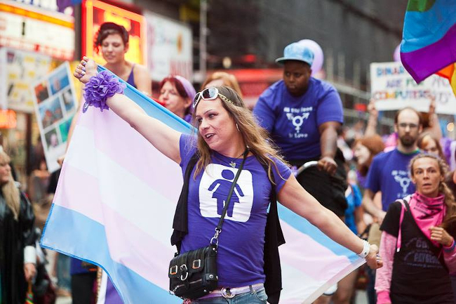 Joyful trans people marching in a parade, waving pride flags.