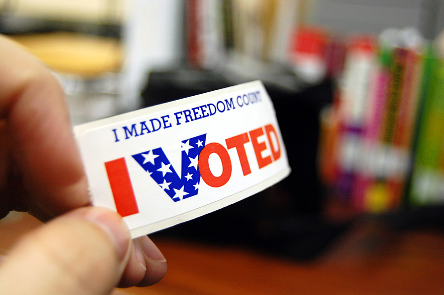 A person holding up an I voted sticker.