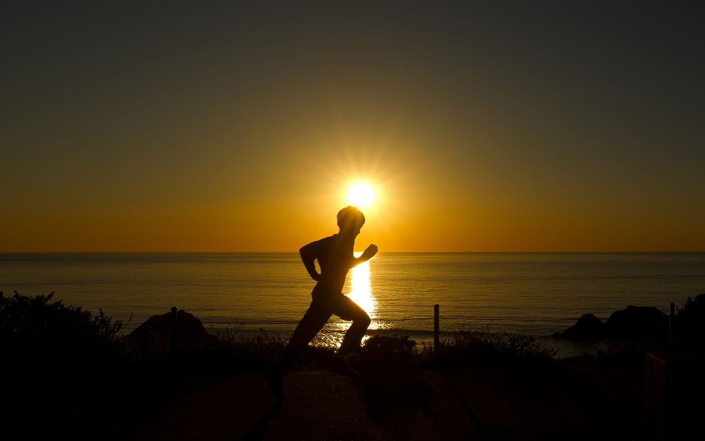A young person running at sunset.