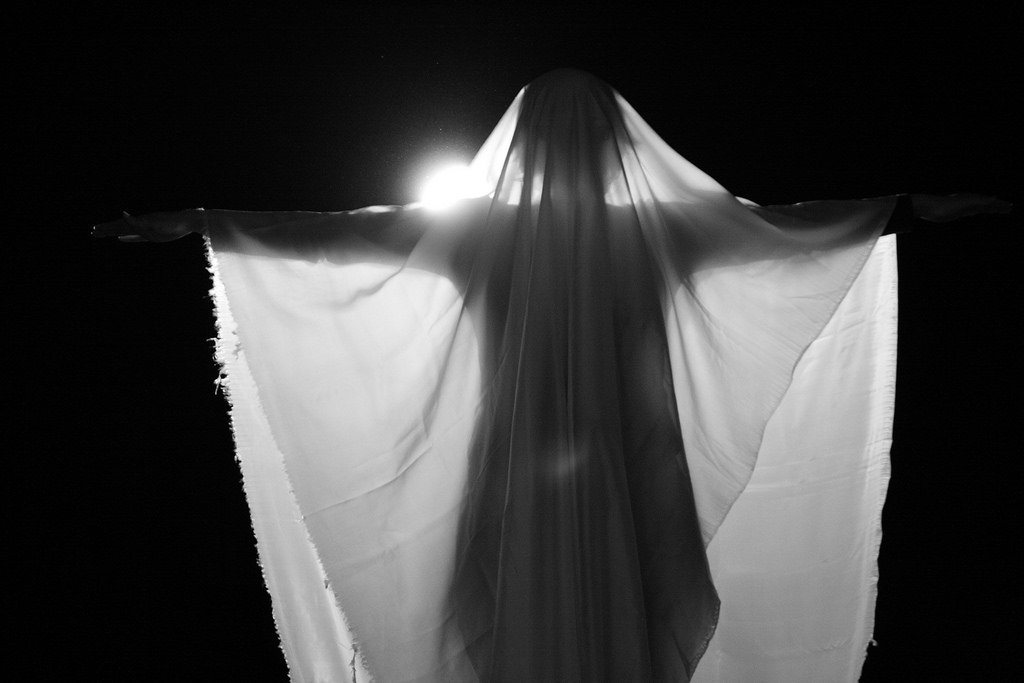 A person draped in a sheet and backlit to look spooky and dramatic.