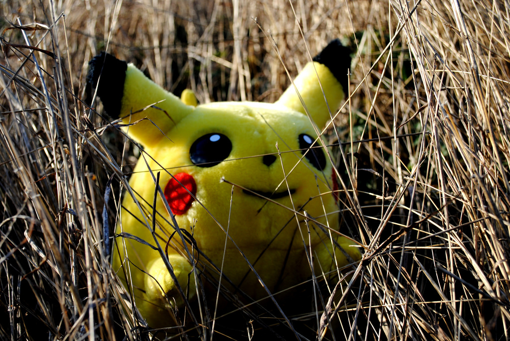 A stuffed Pikachu toy lurking in some grass.