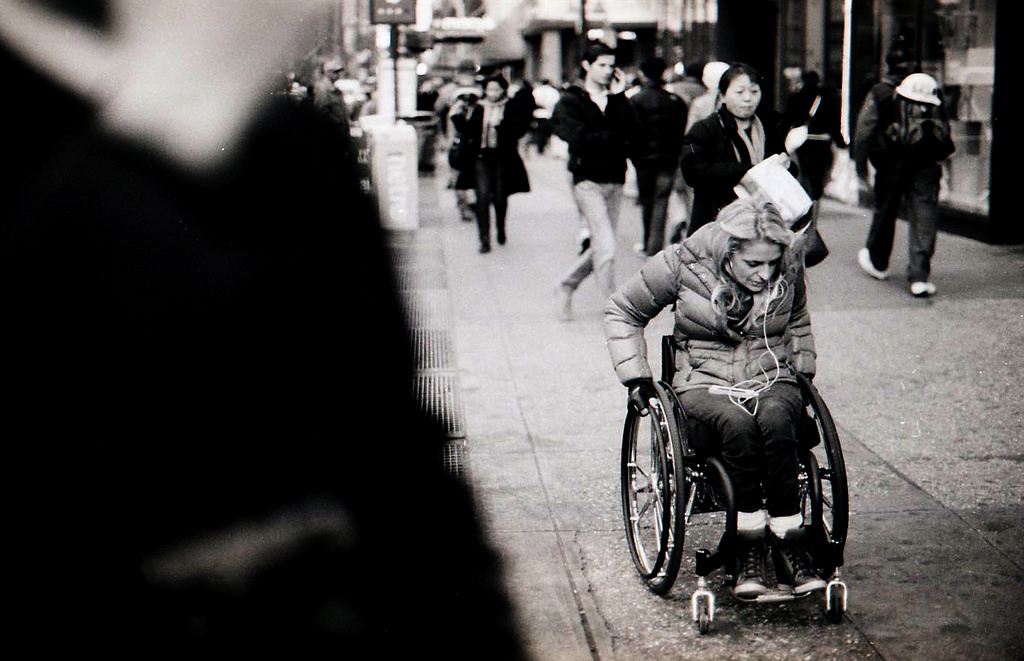 A person in a wheelchair zooming down the sidewalk in New York City.