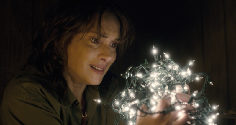 Actor Winona Ryder with a fistful of Christmas lights.