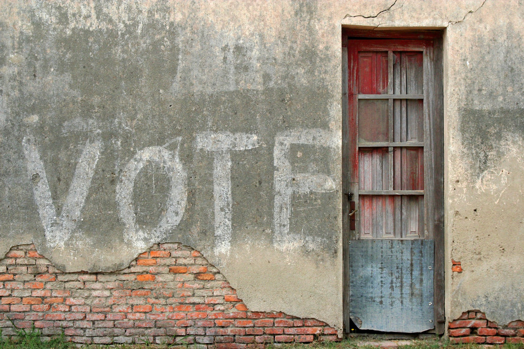 Graffiti exhorting the viewer to vote.