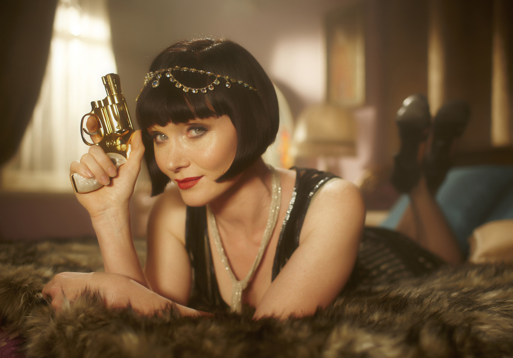 A promotional still from Miss Fisher's Murder Mysteries featuring a woman in lingerie holding a gun.