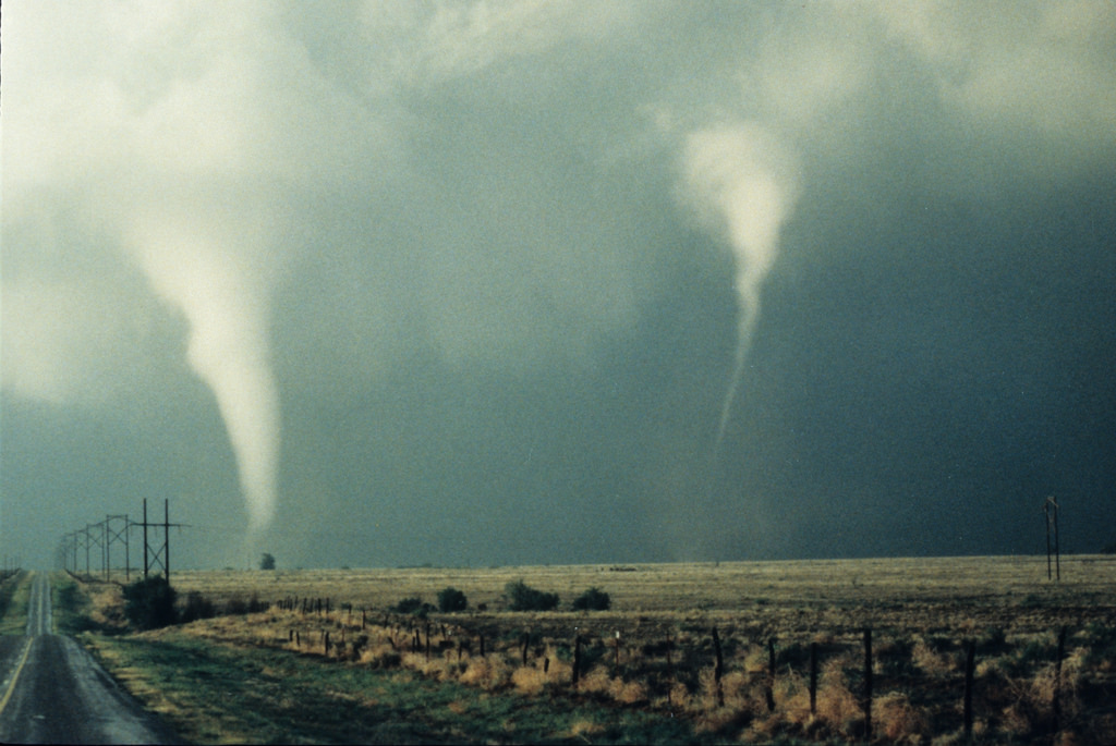 Two tornadoes touching down in an empty field.