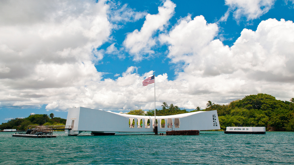 A memorial at Pearl Harbor on a partly cloudy day, flag stiff in the breeze.