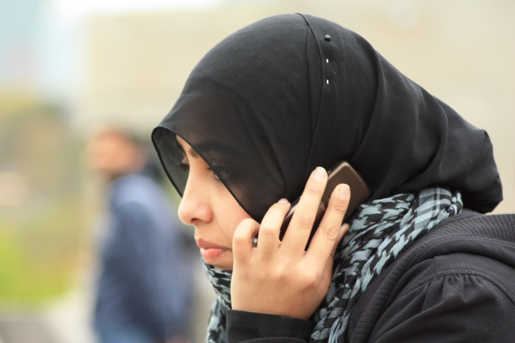 A Muslim woman talking on the phone.