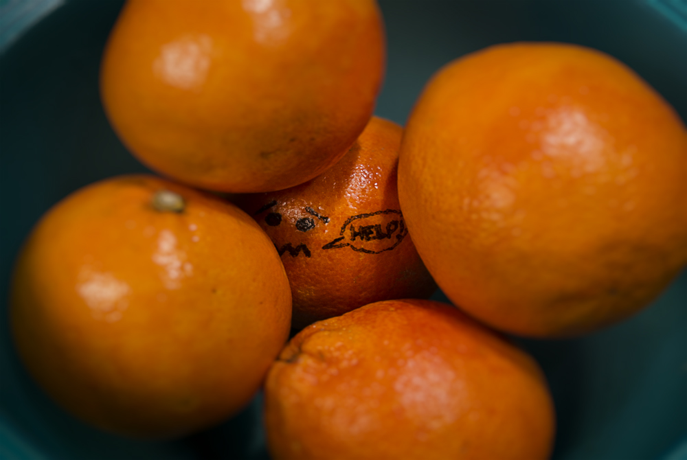 A stack of tangerines. The one at the bottom has been decorated in sharpie with a distressed face and the word HELP.