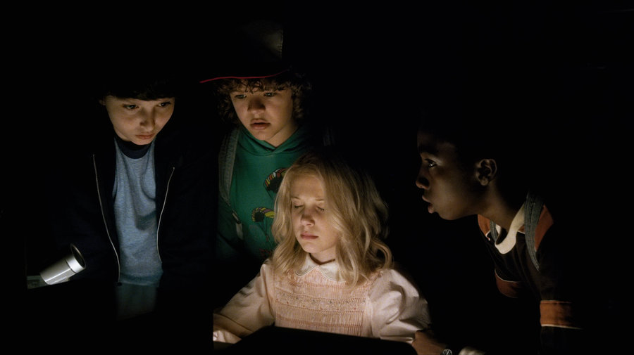 The kids of Stranger Things peering into a screen.