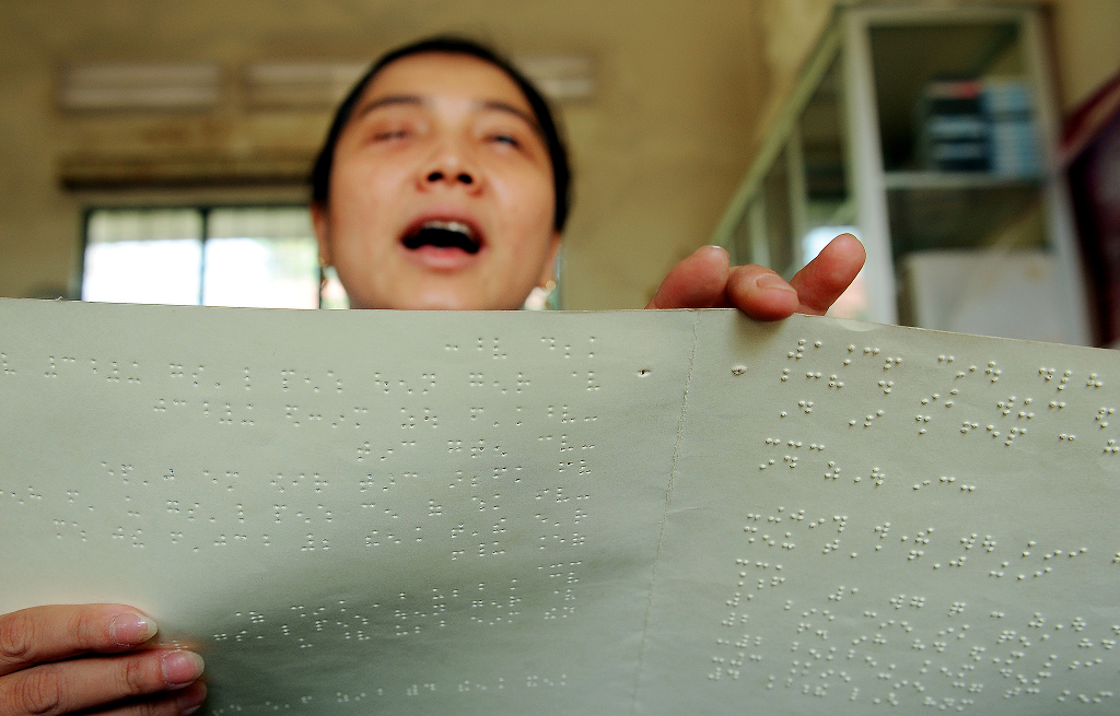A blind person holding up a braille publication as they read.