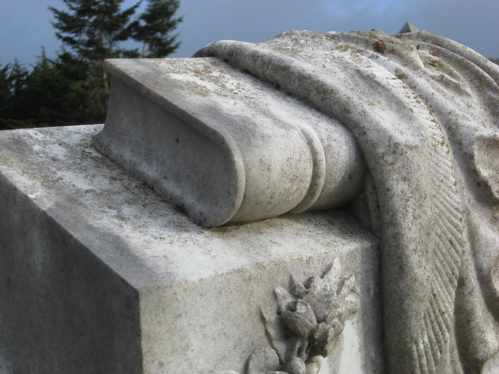 A headstone adorned with a carved book.