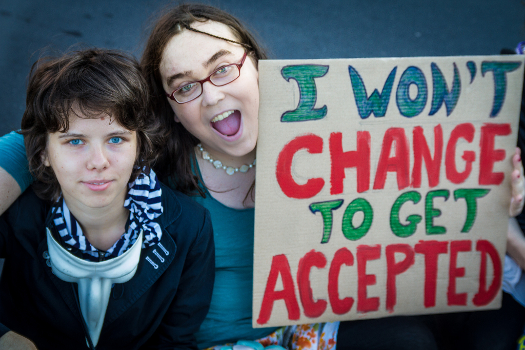 Two people at the Berlin Trans*March holding up a sign saying I WON'T CHANGE TO GET ACCEPTED.