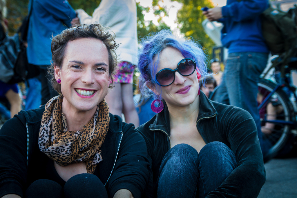 Two smiling people at the Trans*March Berlin, dressed similarly in jeans and black hoodies. One has auburn hair, and the other has purple hair and big sunglasses.