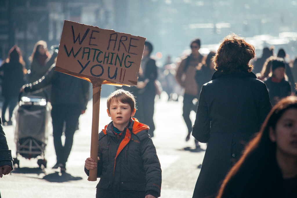 A young protestor holding up a sign that says WE ARE WATCHING YOU