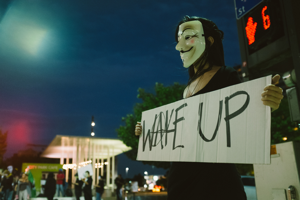 A person in a guy fawkes mask holding up a sign: WAKE UP