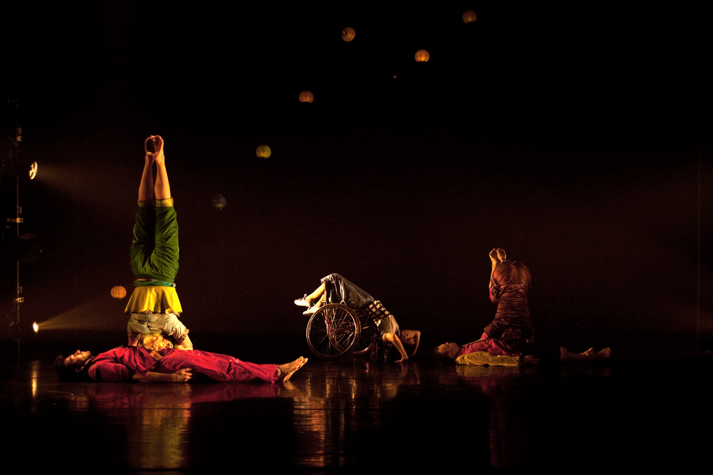 A still from a dancer performance, showing a wheelchair dancer flanked by two people without visible mobility devices, all in fluid poses.