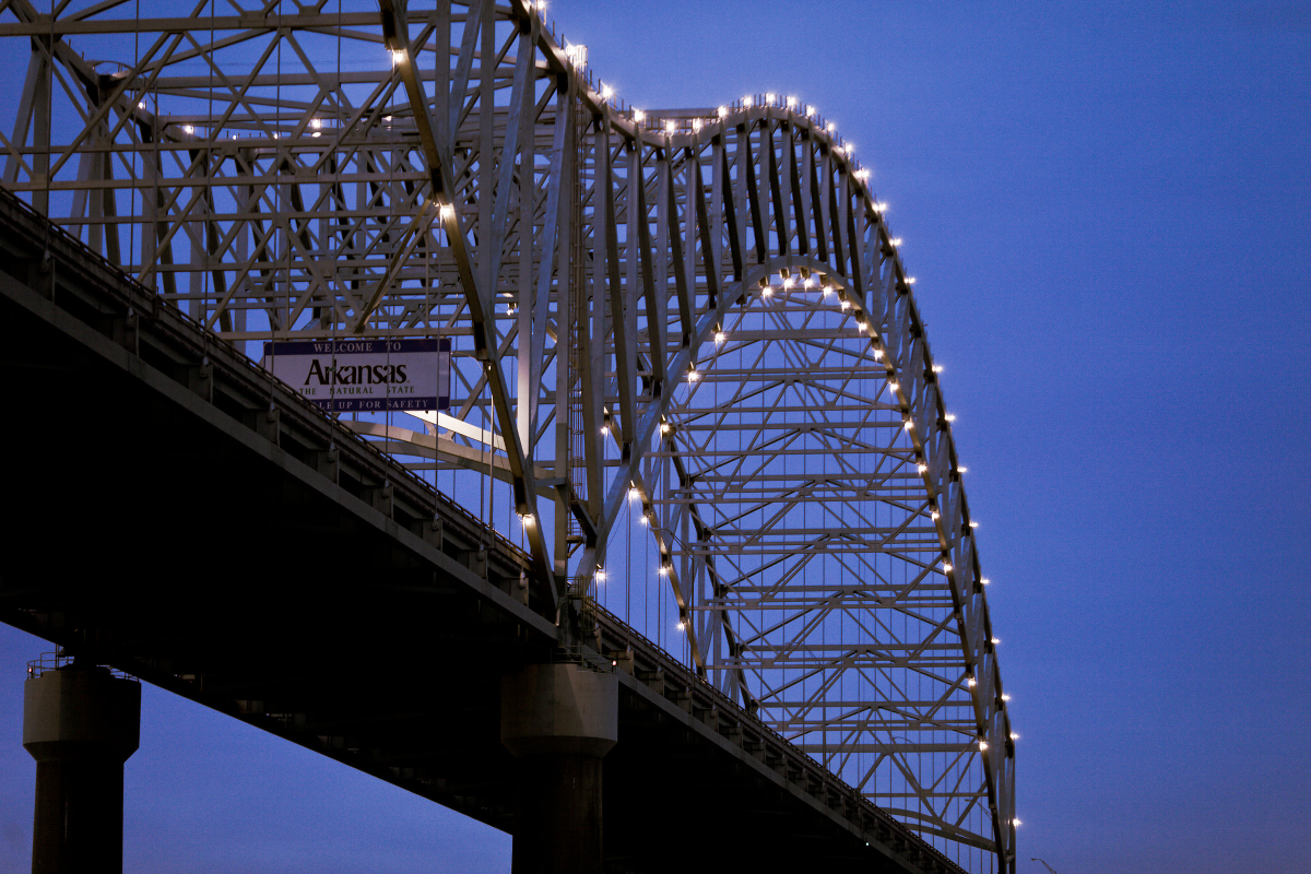 A bridge leading into the state of Arkansas, viewed at night.