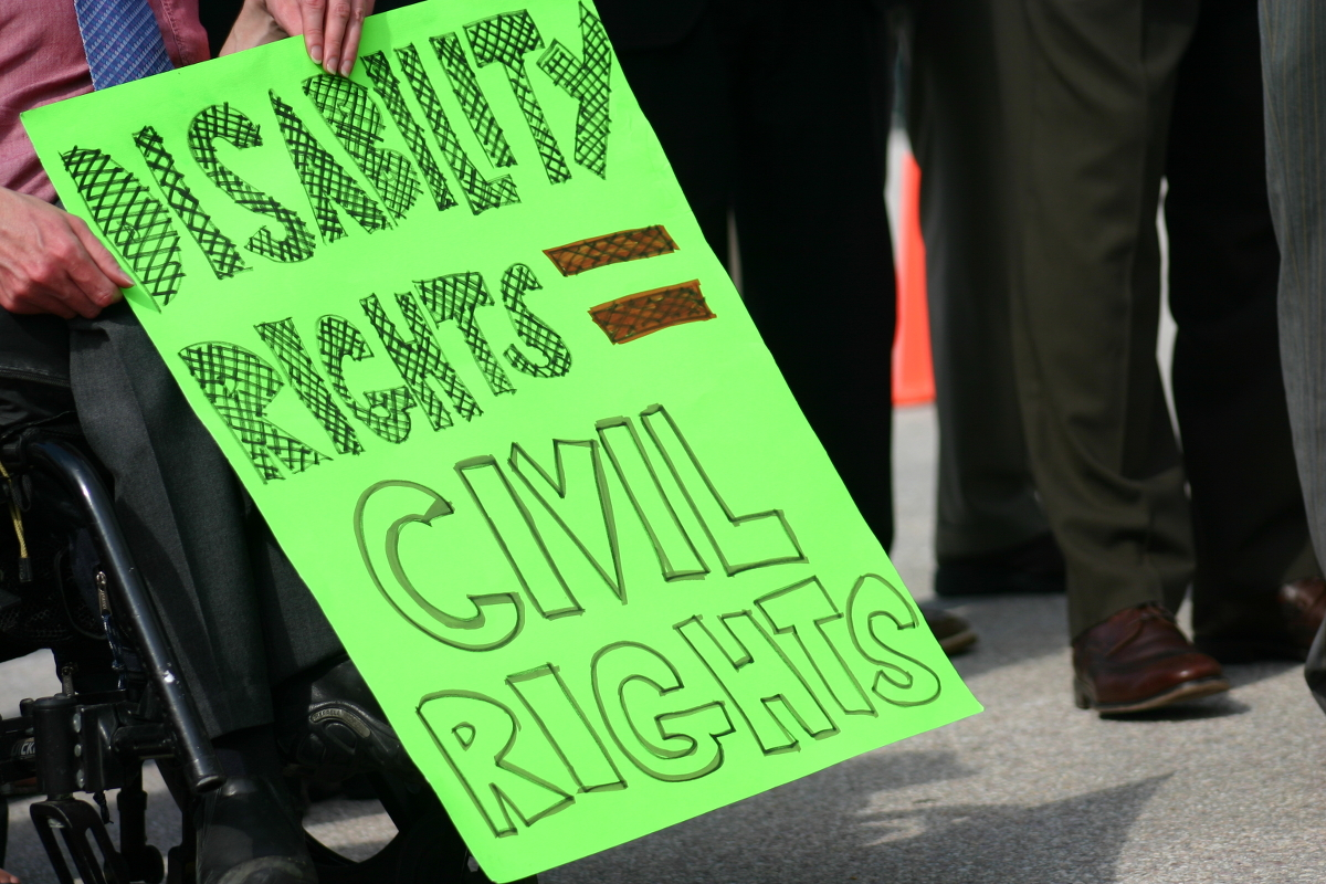 A wheelchair user holding up a sign: DISABILITY RIGHTS ARE CIVIL RIGHTS