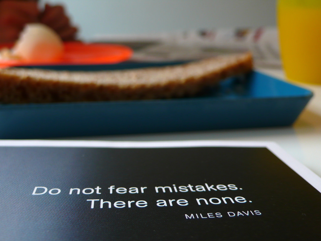 A breakfast table with a book open to a Miles Davis quote: Do not fear mistakes. There are none.