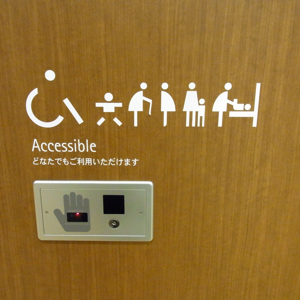 Icons on a bathroom stall indicating that it is accessible and can be used for changing babies as well.