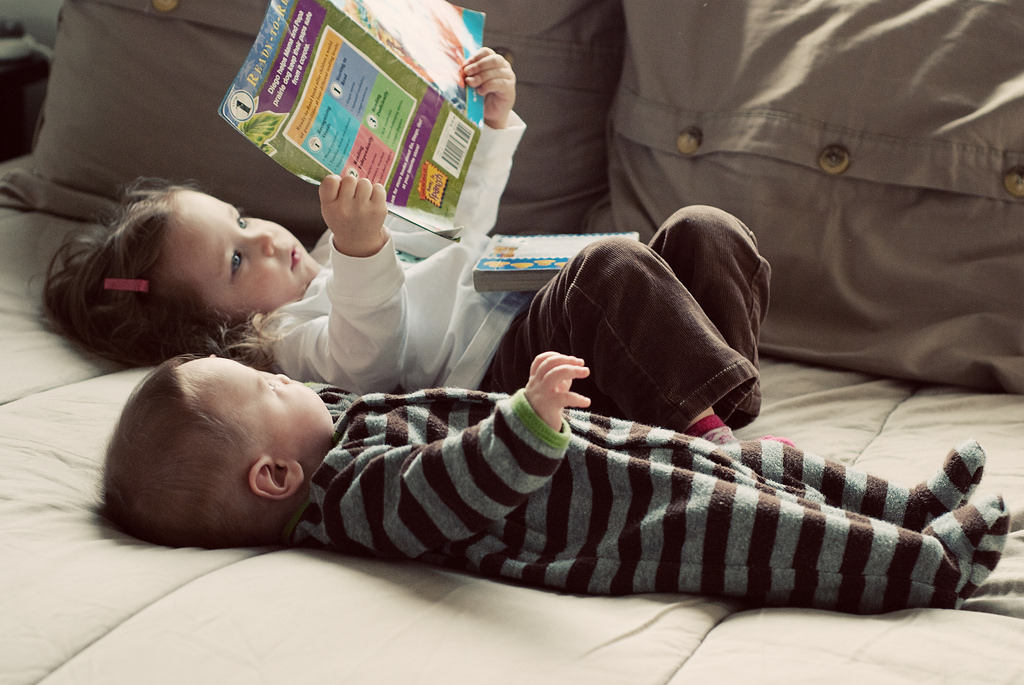 Two young children lying on a couch with a book.