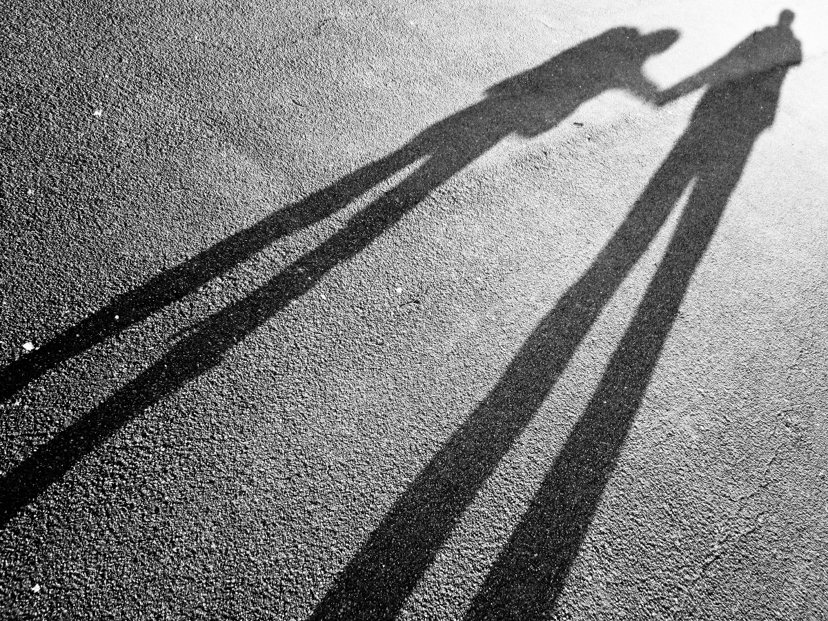 The shadow of a parent reaching for a child's hand.
